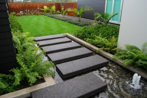 steps over water lead to garden landscape